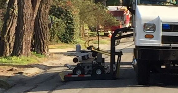 A robot transports the unexploded mortar for detonation at another location.