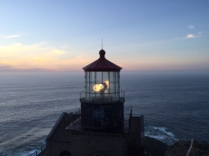 Atop Moro rock, the Point Sur lightstation shines its beam across the coast at twilight.