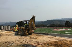 kent-construction-workers-progress-on-stadium-renovations-while-pe-classes-enjoy-use-of-the-field-in-the-background